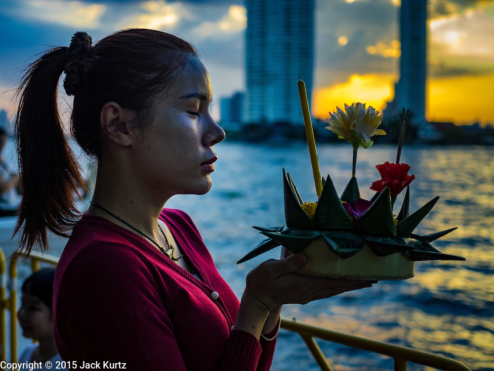 25 NOVEMBER 2015 - BANGKOK, THAILAND: A woman prays before floating her krathong in the Chao Phraya River during Loy Krathong at Wat Yannawa in Bangkok. Loy Krathong takes place on the evening of the full moon of the 12th month in the traditional Thai lunar calendar. In the western calendar this usually falls in November. Loy means 'to float', while krathong refers to the usually lotus-shaped container which floats on the water. Traditional krathongs are made of the layers of the trunk of a banana tree or a spider lily plant. Now, many people use krathongs of baked bread which disintegrate in the water and feed the fish. A krathong is decorated with elaborately folded banana leaves, incense sticks, and a candle. A small coin is sometimes included as an offering to the river spirits. On the night of the full moon, Thais launch their krathong on a river, canal or a pond, making a wish as they do so.     PHOTO BY JACK KURTZ