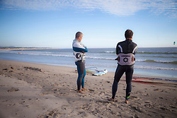 Two surfers looking at sea and standing on the beach, Viana do Castelo, Norte Region, Portugal