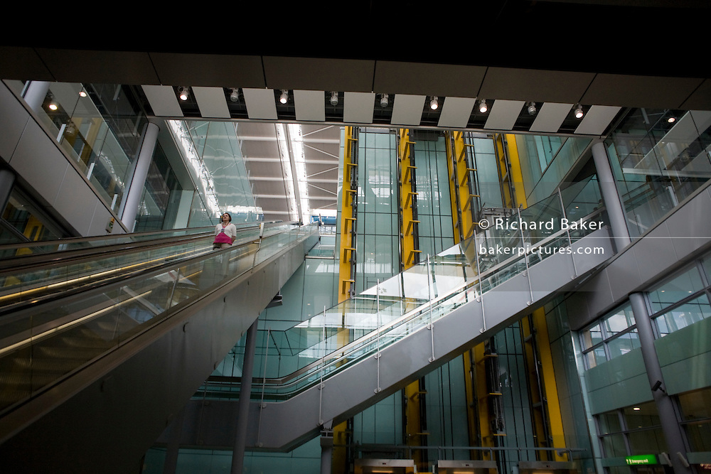 """A lone departing female passenger descends one of the 105 escalators in Terminal 5 of London's Heathrow Airport. Surrounded by the grand architecture created by the Richard Rogers Partnership (now Rogers Stirk Harbour and Partners), we look upwards at this vast atrium that takes passengers through 5A in departures to the outlying gates into Terminal 5B.Terminal 5 has the capacity to serve around 30 million passengers a year, taking £4.3bn to build. From writer Alain de Botton's book project """"A Week at the Airport: A Heathrow Diary"""" (2009). ..."""