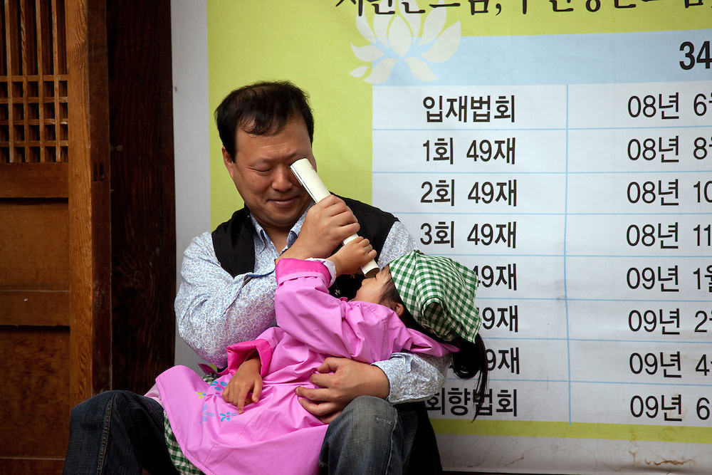 """Vater spielt mit seiner Tochter am Rande der Feierlichkeiten von Buddhas Geburtstag (2. Mai 2009) im Zentrum der koreanischen Netropole Seoul.<br /> <br /> Father is playing with his daughter in the center of the korean capital Seoul during the celebrations of Buddhas birthday (2nd of May 2009) which is celebrated according to the Lunisolar calendar. This day is called """"Seokga tansinil"""", meaning """"the day of Buddha's birthday""""."""