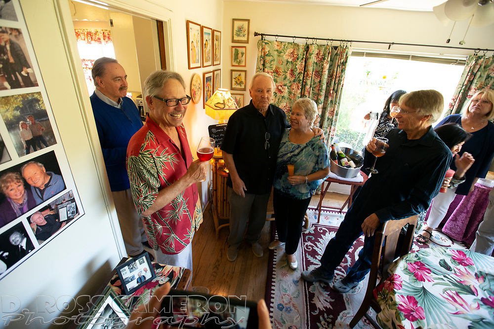 Host Nick Lammers, second from left, leads a toast to the guest of honor at a party celebrating the 80th birthday of long-time Oakland Tribune photographer Ron Riesterer, Sunday, Oct. 21, 2018 in Oakland, Calif. (Photo by D. Ross Cameron)