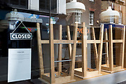 "At the beginning of the fourth week of the UK government's lockdown during the Coronavirus pandemic, and with 120,067 UK reported cases with 16,060 deaths, upturned seats are stacked on tables in the window of 'Eat Activ', a Soho cafe offering ""active-health, fast food,"" on 20th April 2020, in London, England."