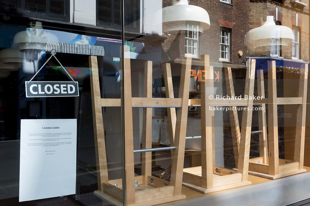 """At the beginning of the fourth week of the UK government's lockdown during the Coronavirus pandemic, and with 120,067 UK reported cases with 16,060 deaths, upturned seats are stacked on tables in the window of 'Eat Activ', a Soho cafe offering """"active-health, fast food,"""" on 20th April 2020, in London, England."""
