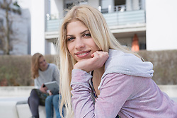 Portrait of teenage girl with her friends using digital tablet in the background, Munich, Bavaria, Germany