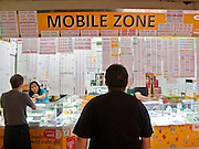 Oct. 9, 2009 -- BANGKOK, THAILAND: Shopping for a phone number in the Mahboonkrong (MBK)  shopping center in Bangkok, Thailand. MBK is an immense six story shopping mall with department stores, restaurants, a hotel and thousands of small shops and stalls. It is more like a vast indoor market than a shopping mall. Thais are firm believers in numerology and frequently try to buy phone numbers they think will bring them the best luck.      Photo by Jack Kurtz / ZUMA Press