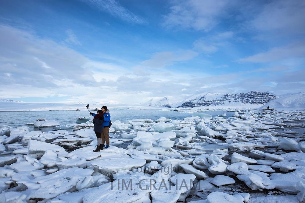 Tourists taking selfie photograph using smartphone for holiday photos at Jokulsarlon glacial lagoon, Vatnajokull National Park, South East Iceland