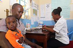 Samuel Otieno and his son Jared with staff member......  the clinic on the ANC day. SAHFA baseline survey visit to Angiya, Homa Bay County, Kenya.  SAHFA Kenya © April 2019