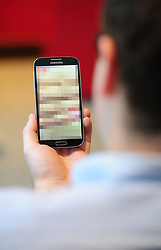 PICTURE POSED BY MODEL<br /> Undated photo of a man looking at a mobile phone. Clarification is needed on the law around &quot;revenge porn&quot; and when it could lead to a prosecution, a committee of peers has said.