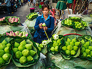 "21 DECEMBER 2015 - BANGKOK, THAILAND:  Selling lotus buds from a street side stand in Pak Khlong Talat, also called the Flower Market. The market has been a Bangkok landmark for more than 50 years and is the largest wholesale flower market in Bangkok. A recent renovation resulted in many stalls being closed to make room for chain restaurants to attract tourists. Now Bangkok city officials are threatening to evict sidewalk vendors who line the outside of the market. Evicting the sidewalk vendors is a part of a citywide effort to ""clean up"" Bangkok.      PHOTO BY JACK KURTZ"