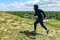 © Licensed to London News Pictures. 11/05/2020. LONDON, UK.  A man exercises at Northala Fields in west London.  The previous day, Boris Johnson, Prime Minister, delivered a speech to the nation relaxing certain aspects of coronavirus lockdown which includes unlimited amounts of exercise outdoors for individuals from 13 May.  Photo credit: Stephen Chung/LNP