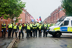 Police officers from the PSU close side streets in Hexthorpe, Doncaster South Yorkshire  to keep opposing EDL and UAF protester apart. The EDL and UAF are thought to have chosen Hexthorpe after recent media reports of tension between newly arrived Roma residents and the the local community<br /> 18 July 2014<br /> Image © Paul David Drabble <br /> www.pauldaviddrabble.co.uk