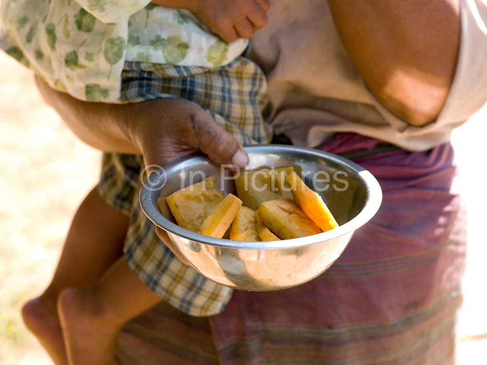 An Intha woman with her young child hold a bowl of freshly made tofu, Kaung Daing, Shan State, Myanmar (Burma). Located on the northwestern shore of Inle Lake, the Intha village of Kaung Daing is known for its tofu, prepared using split yellow peas instead of soybeans.