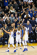Golden State Warriors guard Ian Clark (21) celebrates with  forward Kevin Durant (35) and guard Stephen Curry (30) after hitting a three pointer against the Atlanta Hawks at Oracle Arena in Oakland, Calif., on November 28, 2016. (Stan Olszewski/Special to S.F. Examiner)