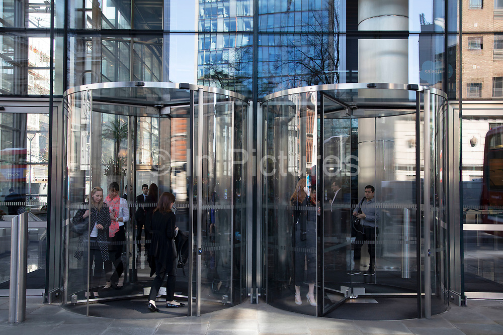Modern glass revolving doors of offices at Heron Tower in the City of London, England, United Kingdom. As Londons financial district grows in height, the architecture has changed the face of Londons financial district, with many different companies occupying the various floors and levels. The Heron Tower, also referred to as 110 Bishopsgate, is a skyscraper developed by Heron International and designed by Kohn, Pederson Fox or KPF.