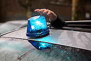 A policeman puts the blue light on roof of an Undercover police car.