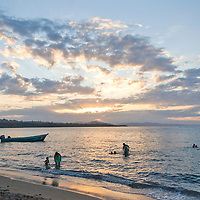 The sun sets as families play in the water, at Manzanillo Beach, Costa Rica. Photo by William Byrne Drumm.