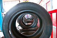 Workers in a tire installation and repair shop are framed through the holes in a row of new tires. WATERMARKS WILL NOT APPEAR ON PRINTS OR LICENSED IMAGES.