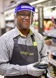 © Licensed to London News Pictures. 15/04/2020. London, UK. Waitrose employee Michael (20yo) wears a face shield while on the shop floor. Staff at Waitrose at Westfield White City are now issued with PPE (personal protection equipment) before starting shift which they are encouraged but not obliged to wear when coming into contact with high volumes of shoppers. The face shields protect the wearer from aerosol ejection, one of the key vectors associated with the transmission of the coronavirus COVID-19. While frontline workers in other sectors notably in healthcare - NHS and care homes - are struggling to access appropriate protection some supermarkets have taken matters into their own hands providing their own PPE and cleaning protocols. Photo credit: Guilhem Baker/LNP
