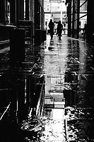 Pedestrians walk through rain-soaked Mitchell Lane towards Buchanan Street, the main shopping street in Glasgow