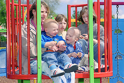 Single mother sitting on climbing frame in playground with young children,