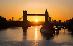 © Licensed to London News Pictures. 19/02/2016. London, UK. A bright orange sunrise behind Tower Bridge in central London on a cold winter morning.  Photo credit: Colin Hart/LNP