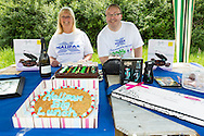 20140601 Free for editorial use image<br /> <br /> Halifax colleagues in Bournemouth are proud to give extra back to their local community by hosting their Big Lunch event on Sunday 01 June 2014.<br /> <br /> Halifax staff Geraldine Martin and Johnny Clark man the raffle stand during The Big Lunch at the New Leaf Allotment in Bournemouth. <br /> <br /> For more information please contact: Catherine Eastham on 020 3697 4304<br /> <br /> If you require a higher resolution image or you have any other onEdition photographic enquiries, please contact onEdition on 0845 900 2 900 or email info@onEdition.com<br /> This image is copyright the onEdition 2014©.<br /> This image has been supplied by onEdition and must be credited onEdition. The author is asserting his full Moral rights in relation to the publication of this image. Rights for onward transmission of any image or file is not granted or implied. Changing or deleting Copyright information is illegal as specified in the Copyright, Design and Patents Act 1988. If you are in any way unsure of your right to publish this image please contact onEdition on 0845 900 2 900 or email info@onEdition.com