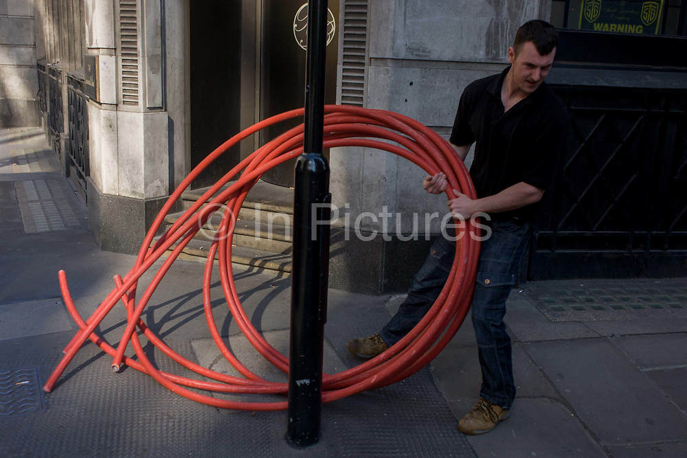 A workman drags a coil of heavy piping or cable sleeves through a street in the City of London. Holding the length of red materials, he pulls at the weight across the path on a street corner near the Bank of England. Coincidentally, we see the halving of two circles - the piping as well as the logo on a background doorway.