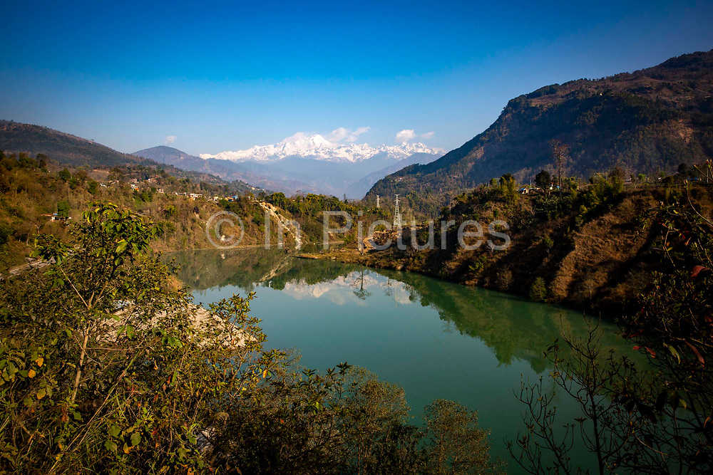 The wide part of the Marsyangdi river just north of the Mid-Marsyangdi hydro electricity dam on the 8th of March 2020  Lamjung District in Gandaki Pradesh, Nepal. The Mid-Marsyangdi hydro electricity plant produces 72MW  of power and saves around 340,000 tonnes of CO2 emissions annually.