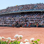 2017 French Open Tennis Tournament - Day Fourteen.  A panoramic view of Jelena Ostapenko of Latvia in action against Simona Halep of Romania in the Women's Singles Final match on Philippe-Chatrier Court at the 2017 French Open Tennis Tournament at Roland Garros on June 10th, 2017 in Paris, France.  (Photo by Tim Clayton/Corbis via Getty Images)<br /> <br /> Note to Editors. This image is a composite of two images taken a split second apart and merged in editing.