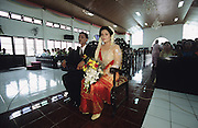 Bride and groom sitting in church. Wedding in Medan..Batak Indigenous Christian people living on Samosir Island and nearby Lake Toba in Indonesia. There are some 6 million Christian Batak in Indonesia, the world's largest Muslim country of 237 million people, which has more Muslims than any other in the world. Though it has a long history of religious tolerance, a small extremist fringe of Muslims have been more vocal and violent towards Christians in recent years. ..Batak religion is found among the Batak societies around Lake Toba in north Sumatra. It is ethnically diverse, syncretic, liable to change, and linked with village organisations and the monotheistic Indonesian culture. Toba Batak houses are boat-shaped with intricately carved gables and upsweeping roof ridges, and Karo Batak houses rise up in tiers. Both are built on piles and are derived from an ancient Dong-Son model. The gable ends of traditional houses, Rumah Bolon or Jabu, are richly decorated with the cosmic serpent Naga Padoha carved in wood or in mosaic, lizards, double spirals, female breasts, and the head of the singa, a monster with protruding eyes that is part human, part water buffalo, and part crocodile or lizard. The layout of the village symbolises the Batak cosmos. They cultivate irrigated rice and vegetables. Irrigated rice cultivation can support a large population, and the Toba and the Karo live in densely clustered villages, which are limited to around ten homes to save farming land. The kinship system is based on marriage alliances linking lineages of patrilineal clans called marga. In the 1820's Islam came to the southern Angkola and Mandailing homelands, and in the 1850's and 1860's Christianity arrived in the Angkola and Toba region with Dutch missionaries and the German Rheinische Mission Gesellschaft. The first German missionary caused the Dutch to stop Batak communal sacrificial rituals and music, which was a major blow to the traditional religion. Dutch colonial policy favou