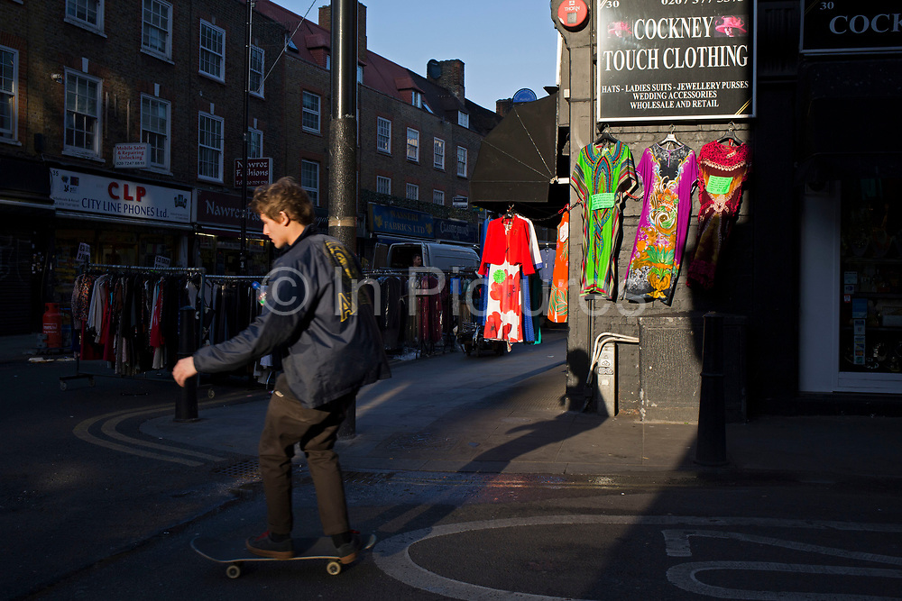 Evening light in the City of London as a skateboarder passes at Petticoat Lane Market, England, United Kingdom.