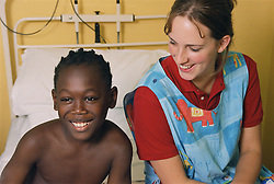 Staff nurse sitting with young patient on hospital bed on children's medical ward,