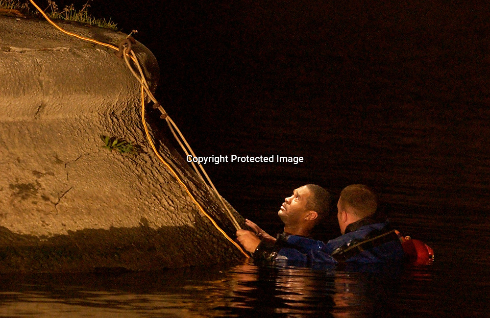 A dive team member talks with an unidentified man holding onto the Jefferson Street bridge footing after he jumped into the St. Joseph River on Tuesday night. <br /> Santiago Flores/ photo/ news<br /> 071002
