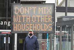 """© Licensed to London News Pictures. 30/09/2020. Bolton, UK. A man wearing a facemask walks past a sign reading """"DON'T MIX WITH OTHER HOUSEHOLDS"""", in Bolton, North West England. Photo credit: Kerry Elsworth/LNP"""