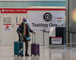 """© Licensed to London News Pictures. 24/11/2020. London, UK. A passenger walks past a Covid testing centre at London Heathrow Terminal 5 today. Minister for Transport Grant Shapps has announced that quarantine for air travellers will drop to 5 days from mid December if they take a private Covid test. Under the new """"test to release"""" scheme passengers who test negative after 5 days self-isolation will be able to carry on with their normal lives. Photo credit: Alex Lentati/LNP"""