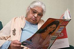 Elderly Asian woman reading the newspaper,