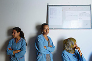 Women take a break while working at a textile factory in Soliman, Tunisia. The factory produces clothes for Saks Fifth Avenue, Neiman Marcus, Benetton and Gant, among other clothing companies. The factory is considered off-shore and only exports, so it does not pay tax to Tunisia. Women work 48 hours each week and earn an average of $250 a month. Most left school early to earn money for their families.