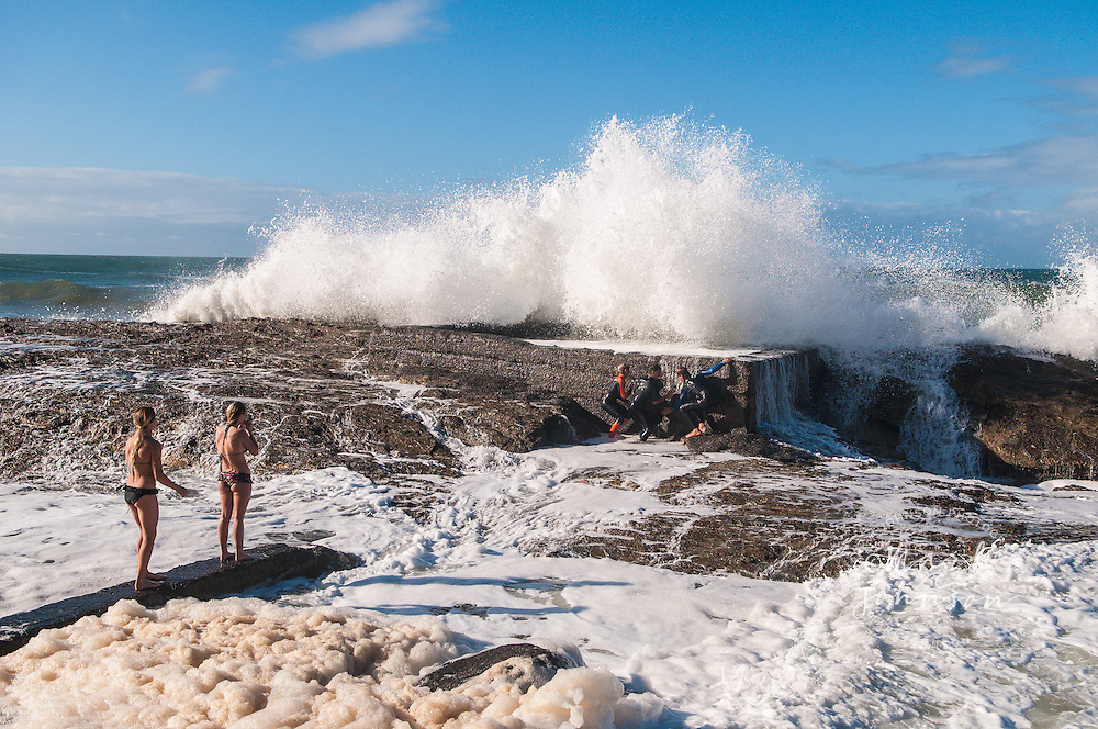 Boys playing with big surf & girls watching at Snapper Rocks, Gold Coast, Queensland, Australia people