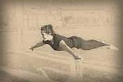 woman is balanced on feet during an Acro Yoga practice session. Digitally enhanced image