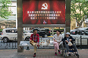 Street scene Shanghai, Communist party and consumer advertising with saenior citizens