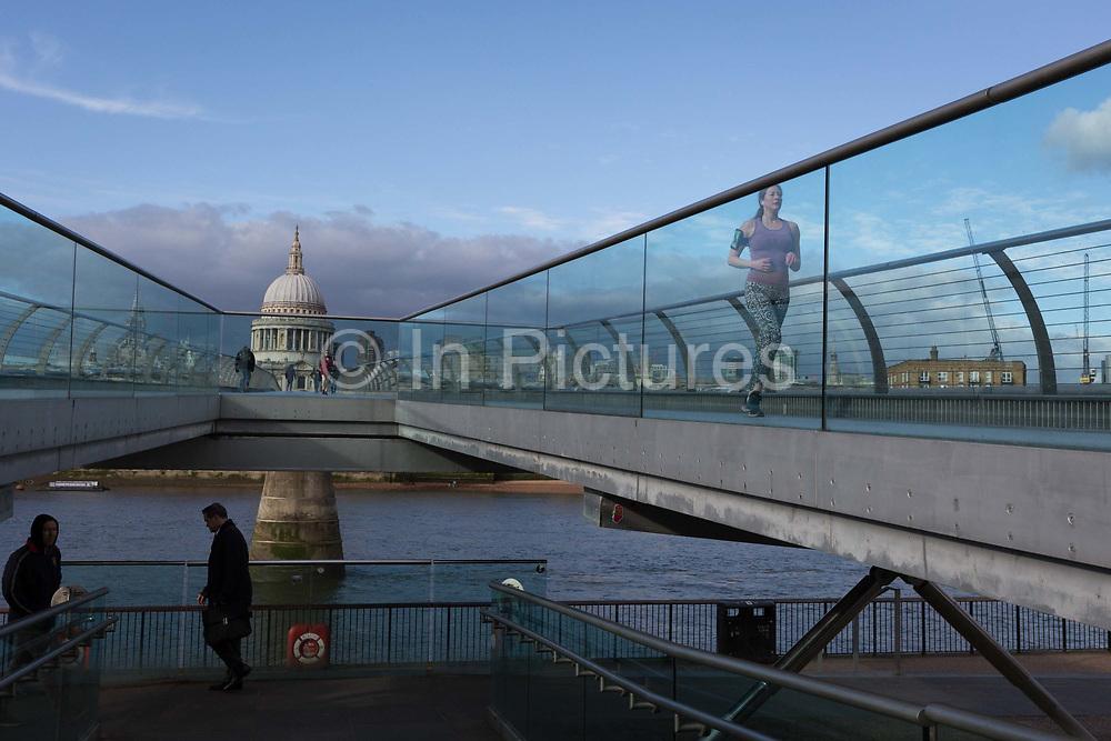 As the UK government announces further Coronavirus-related restrictions to its citizens, with the immediate closure of pubs, cafes, gyms and cinemas, and the worldwide number of deaths reaching 10,000 with 240,000 cases, 953 of those in London alone, aprt from a runner, the Millennium Bridge remains quiet and largely un-used, on 20th March 2020, in London, England.