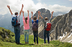 Father teenage kids standing summit Alps
