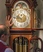 """© Licensed to London News Pictures. 23/10/2014. Guidford, UK. Michael Tooke changes one of his favourite clocks in the shop. As British Summer Time comes to an end, staff at Horological Workshops start the task of changing the 100's of clocks at their store in Guildford, Surrey, UK. Michael Tooke who has owned the store for over 40 years and worked in the clock business all his life said. """"at this time of year we get a lot of people who bring clocks in for repair after they have changed the time incorrectly by winding back the hands manually"""". Clocks change on Sunday morning 26th October. Photo credit : Stephen Simpson/LNP"""