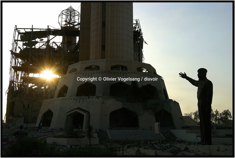 Iraq. Baghdad. Telecommunication building destroyed by the coallition with a statue of Saddam Hussein still stand up. ©
