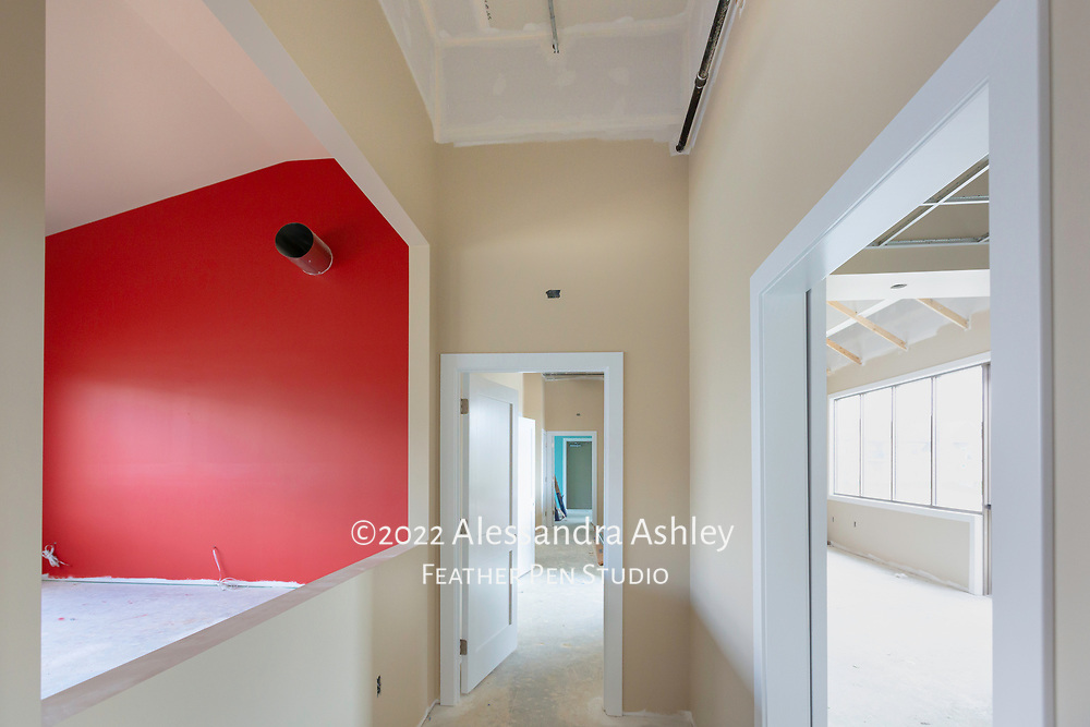 Interior wall painting begins at building site of new physical therapy and wellness center. From hallway (tan color), gymnasium accent wall (red) and yoga room (aqua) are visible. To the right, the lobby space is also painted tan.