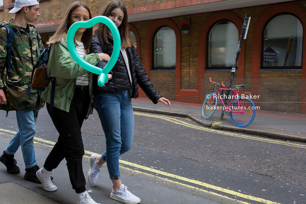 Two girls carrying a green heart-shaped balloon walk past a multi-coloured bike is locked to a post in a sidestreet in London's West End, on 29th April 2019, in London, England.