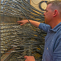Dr. Gregg Hallinan examines the mass of cables running between his radio telescopes and the computer at the Long Range Array at OVRO.