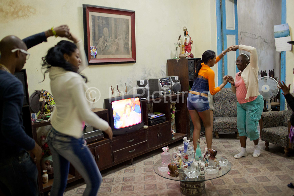 Cuban Santero family dancing Salsa in their house. Santeria is a syncretic religion practiced in Cuba, it is a mixture of Yoruba tribal practices brought from Nigeria during Colonial times, and traditional Catholic beliefs. During this time, the slaves used the images of saints to cover up their worship of the Orishas (spirits)