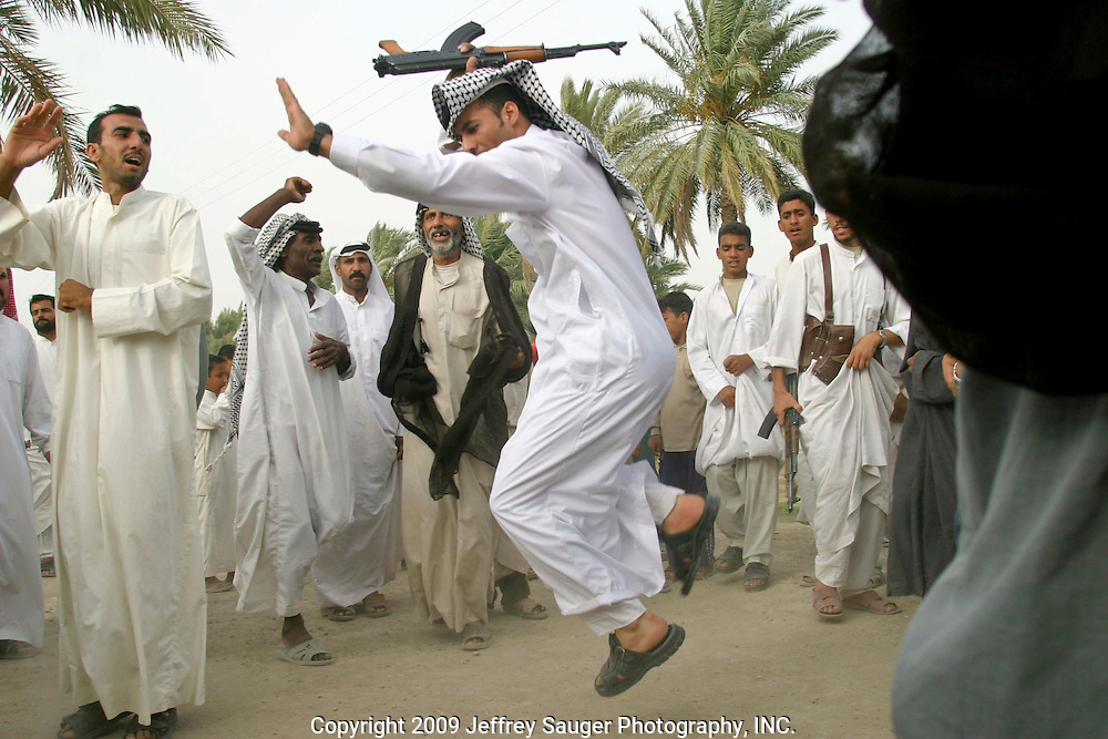 Emad Al-kasid, with rifle in air, performs Hawaies, a traditional tribal Arabic dance, at the Al-kasid family's Istikbal in their home village Suq ash Shuyukh about 20 miles southeast of Nasiriyah, Iraq, Tuesday, July 29, 2003....The Al-kasid family fled Iraq after the Gulf War and their part in the uprising against Saddam Hussein in 1991, spent 3 years in Rafa, Saudi Arabia and finally settled in Dearborn, MI. The family hasn't been home to Iraq in 13 years.