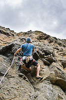 A  male rock climber pulling up rope to clip in to protection. Lava Point, Tieton River Climbing, Cascade Mountain, Washington, USA.
